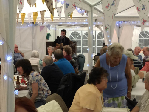 members enjoying the meal and entertained by a local busker