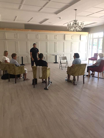 New Friday Keep Fit group of people are seated and practising arm chair exercises